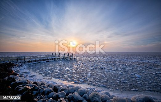 In the early morning at a frozen lake during sunrise. The jetty and its poles are covered with ice due to the water which had been blown on the jetty and poles by wind force before the lake was frozen.