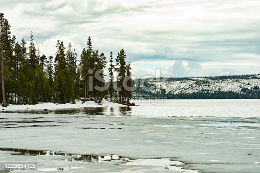 This photograph is of a partially frozen lake with thin ice in Yellowstone national park on a cold overcast spring day.