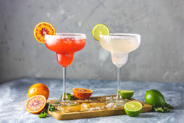 Frozen lime margarita and blood orange margarita cocktail mix in salt rimmed glasses garnished with slices of lime and orange. Focus on the citrus slice stock photo