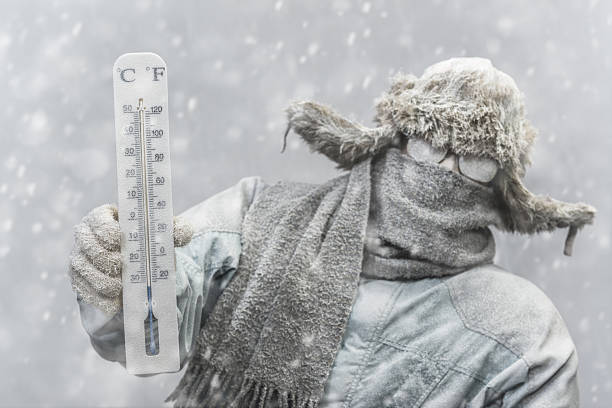 Frozen man holding a thermometer while it is snowing - foto de stock