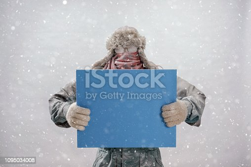 A Caucasian man looking at the camera while holding a blank blue sign while bundled up in a fur trapper's hat, red scarf, parka and gloves, covered in frost while it is gray and snowing outside.