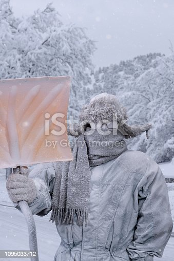 A frozen Caucasian male, all bundled up in a fur trapper's hat, parka, scarf and gloves, wearing glasses looking at the camera and holding a yellow snow shovel, covered in snow and frost from shoveling snow with snow covered trees in the background.