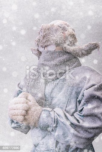 A frozen man with his hands clasped all bundled up in a fur trappers hat, scarf, parka and knit gloves, covered in snow and frost trying to stay warm on a very cold Winter's day as a blizzard's  snow falls around him.