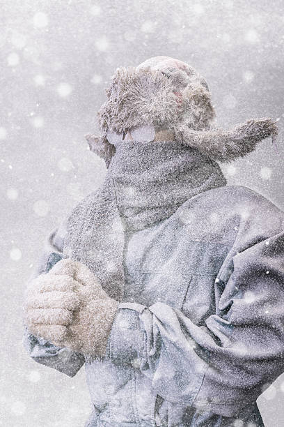 Frozen man in parka, hat and scarf as snow falls stock photo
