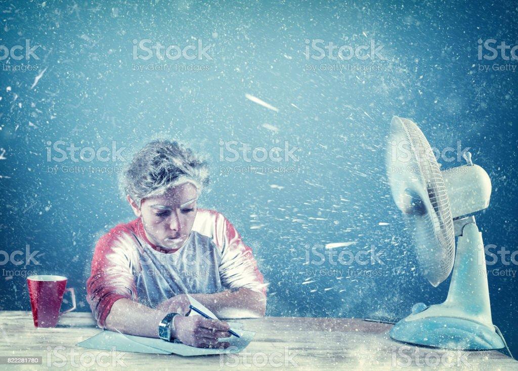 Frozen man working at office beside a powerful fan stock photo