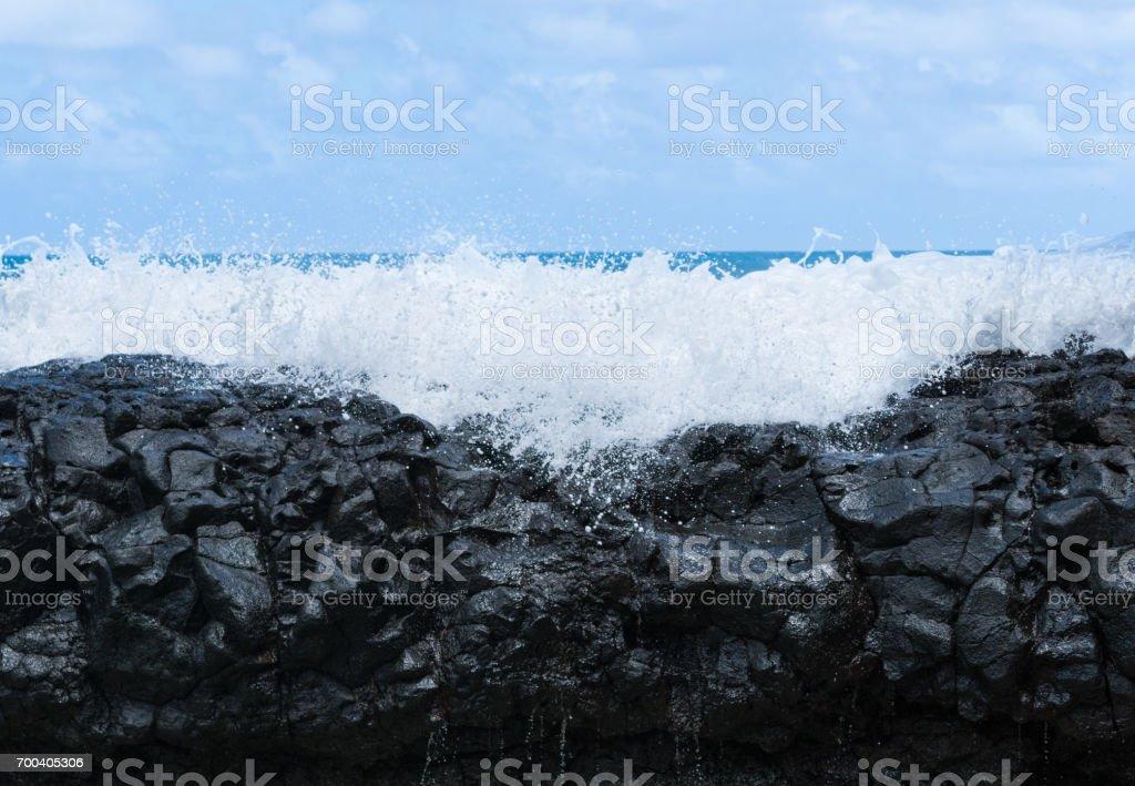 Frozen motion of ocean waterfall over rocks at Lumahai Beach stock photo