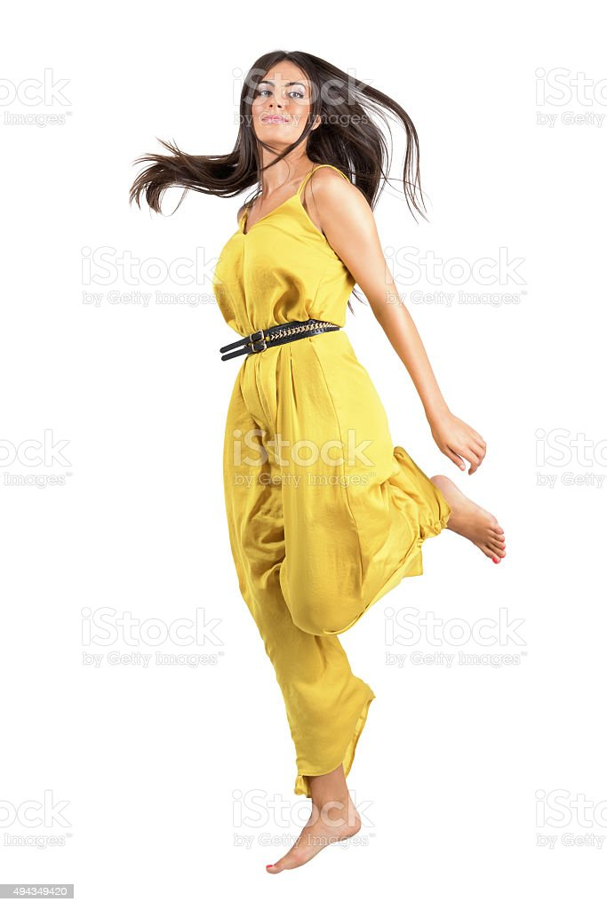 Frozen motion of young beautiful woman in yellow jumpsuit jumping stock photo