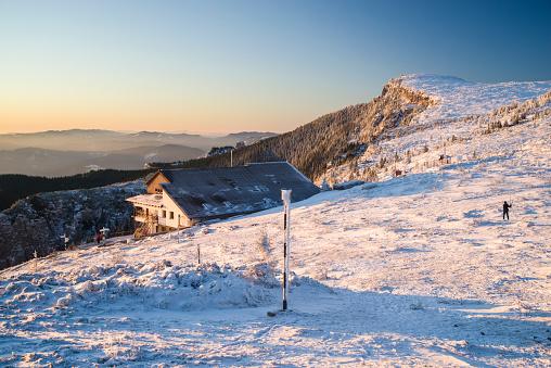 Frozen mountain scene at sunrise, chalat and tourists in Romanian Carpathians.