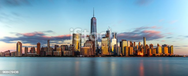 A long exposure panorama of downtown New York skyline during a beautiful sunset.