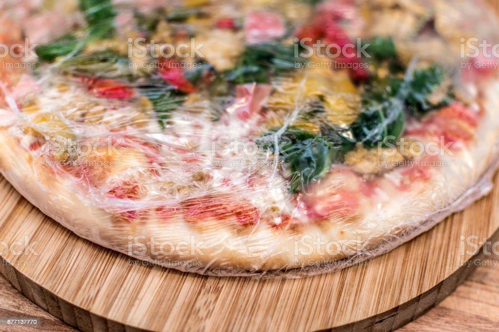 Frozen pizza still in plastic wrap on a board stock photo