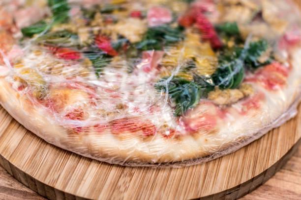아직 보드에 플라스틱 포장에에서 냉동된 피자 - 냉동식품 뉴스 사진 이미지