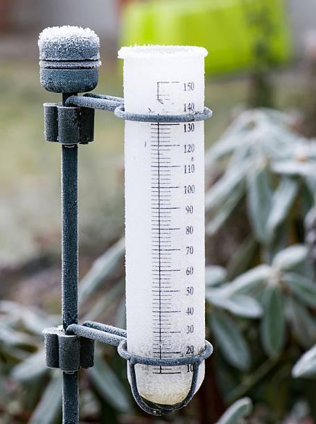 frozen rain gauge in the garden - rain gauge stock photos and pictures