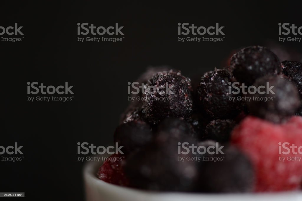 Frozen raspberries and blueberries on a dark background close up stock photo