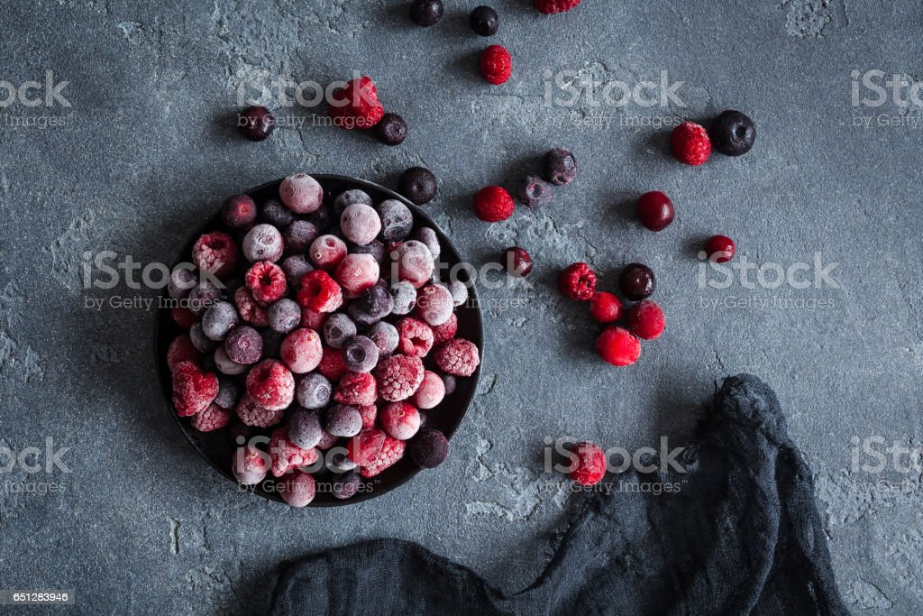 Frozen raspberry, blueberry, cranberry on dark background stock photo
