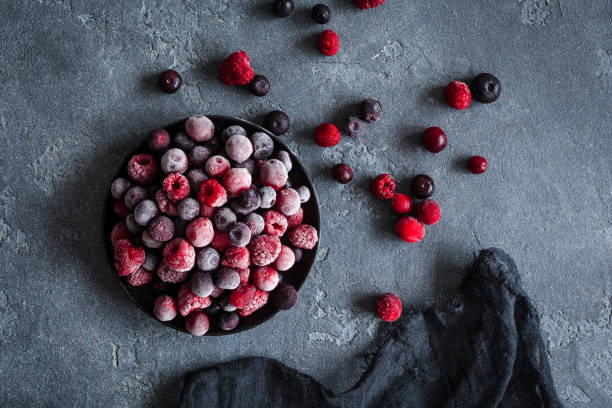 frozen raspberry, blueberry, cranberry on dark background - berry stock photos and pictures