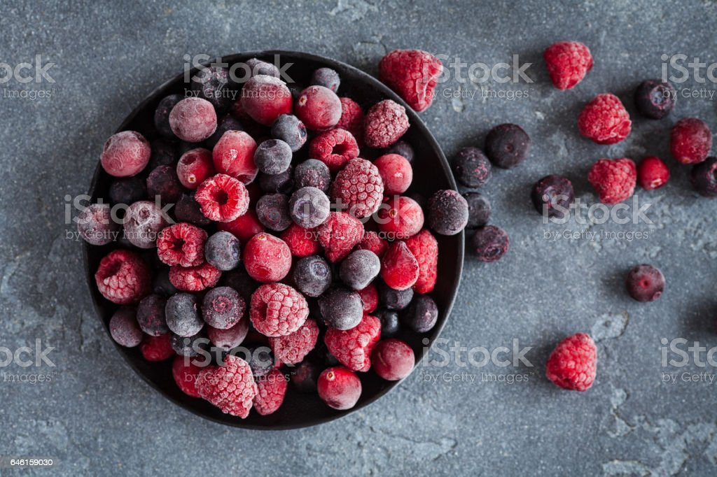 Frozen raspberry, blueberry, cranberry on grunge background stock photo