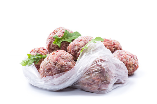 frozen raw meatballs from beef and pork with carrots and rice isolated on white background