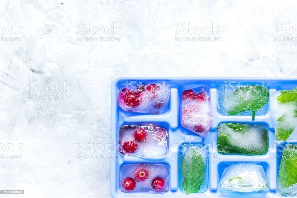 frozen red berries in ice cubes in tray on stone background space for text top view royalty-free stock photo