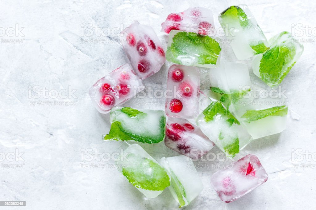 frozen red berries in ice cubes on stone background top view royalty-free stock photo