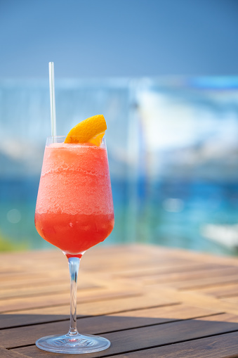 A frozen red cocktail (could be a mai tai, or a hurricane, a rum runner or a strawberry daiquiri) garnished with an orange slice sits on a lake side wooden table. The vibrant greens and blues of the water in the background.