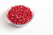Frozen red currant on a white background. Red frozen berries in a bowl. Healthy diet. Copy space.
