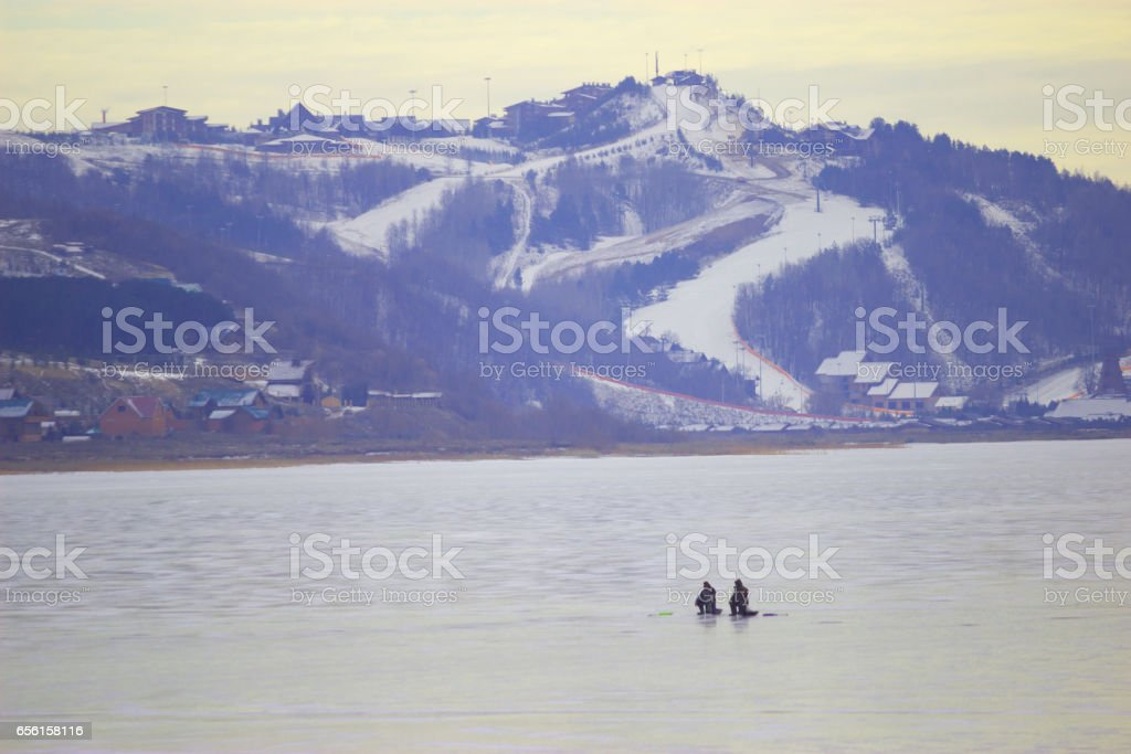 Frozen River and distant mountains stock photo