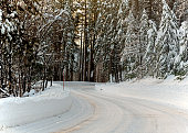 Unplowed mountain road highway 120 towards Yosemite, California, USA, on a winters day featuring snow on the road as a sign of dangerous driving conditions