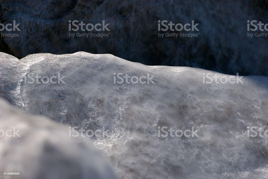 Frozen sea spray glazed rocks stock photo