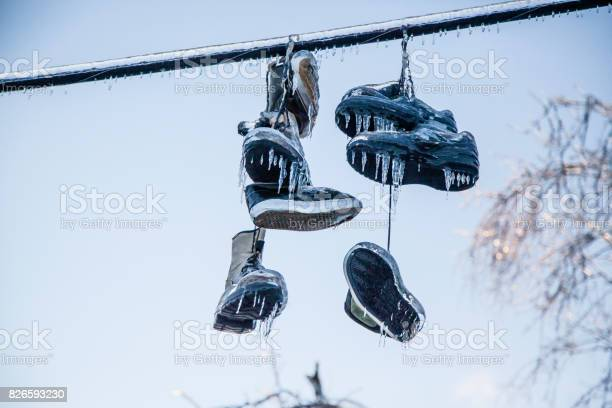 Photo of Frozen Shoes on a line are covered in ice from an ice storm. Many icicles have formed and they are sunlit with this layer of ice.
