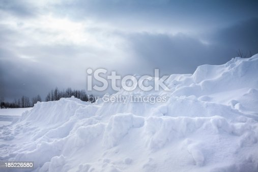 Cold snow drift under the sun and clouds