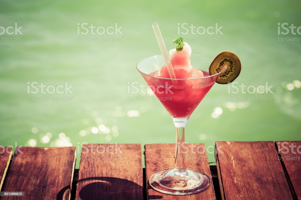 Frozen Strawberry Daiquiri cocktail on the wooden pier. Concept of classic cocktail. Vacation background. stock photo