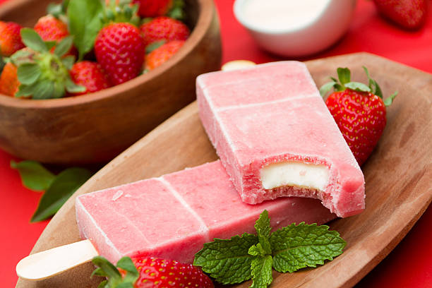 Frozen strawberry popsicles amidst fresh strawberries Stick ice cream strawberry flavor amidst stock pictures, royalty-free photos & images