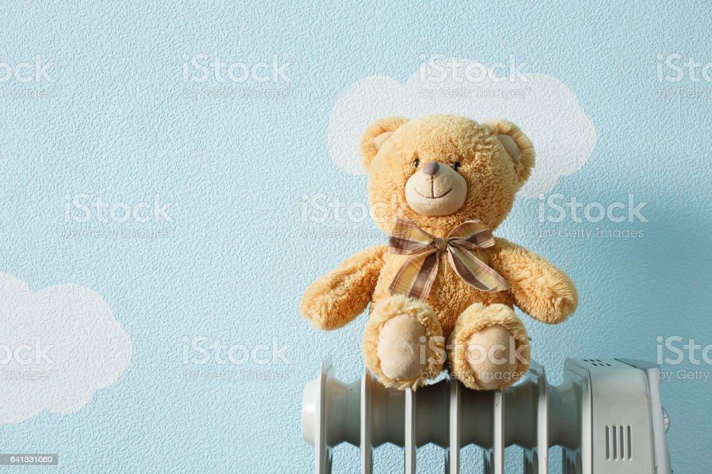 Frozen toy white polar bear sit on the heater stock photo