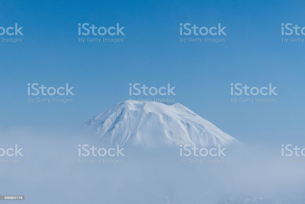 Frozen Volcano poking through the Clouds stock photo