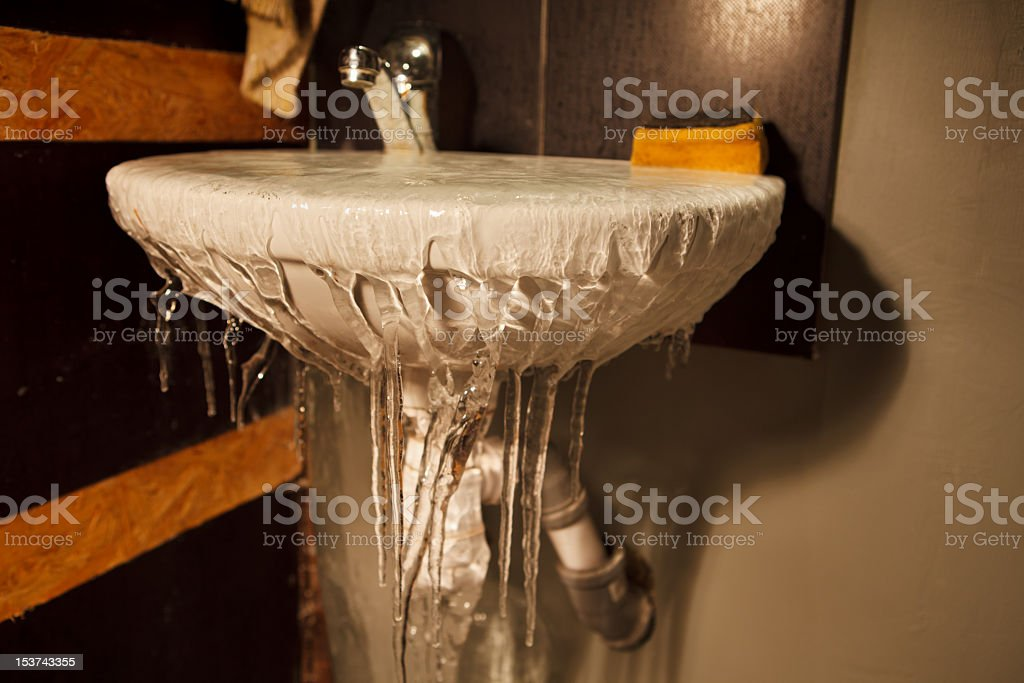 Frozen water spilling out of restroom sink stock photo