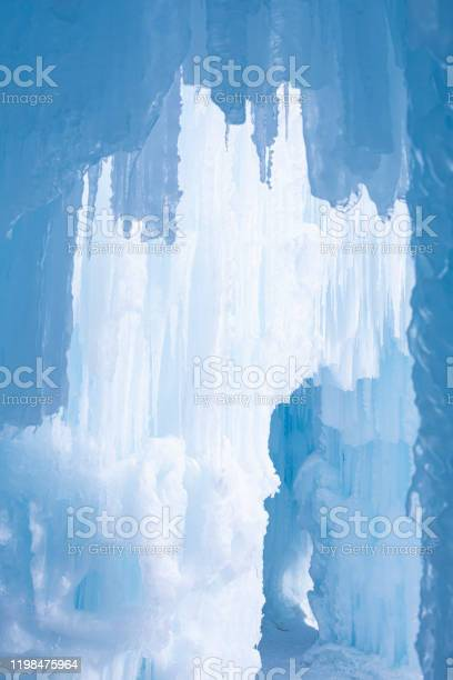 Photo of Frozen winter ice background in blue and white