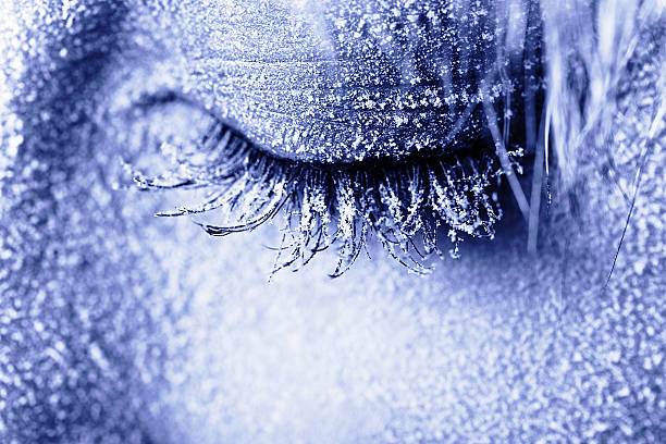 Frozen woman's eye covered in frost stock photo