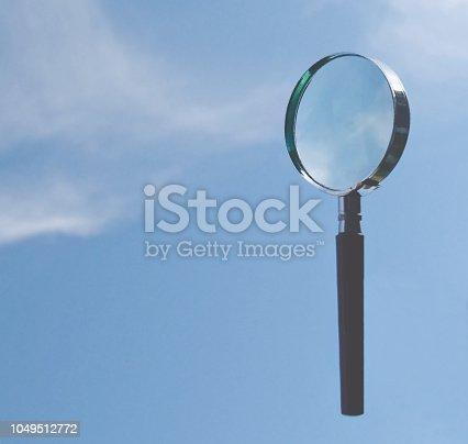 Förstoringsglas mot blå himmel med moln där plats för text kan sättas.