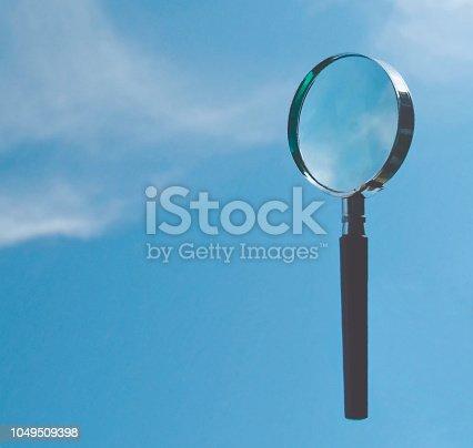 Förstoringsglas mmot cyanblå himmel med moln som flyter in mot fokus och kan användas för text