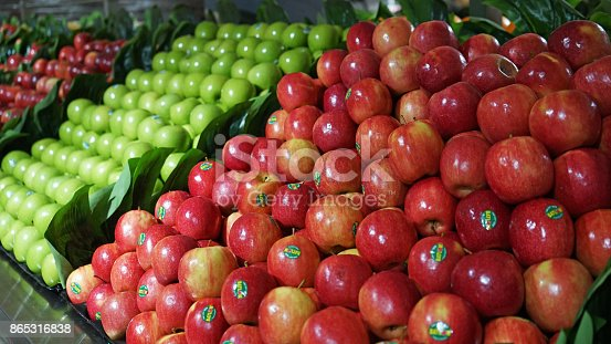 Fruit aisle with piles of red and green apples in the supermarket