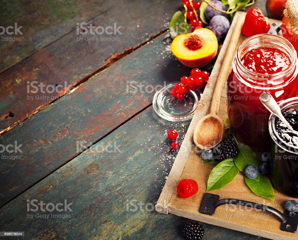 Fruit and berry jam on a wooden background stock photo