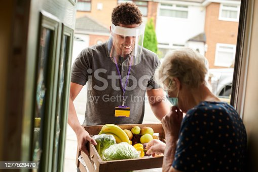 a young volunteer visits an elderly resident with his facemask on delivering fresh produce