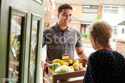 a young volunteer visits an elderly resident  delivering fresh produce