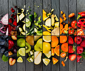 Top view of rainbow colorful mix stripes with fruits and vegetables on gray slate surface; healthy eating concept
