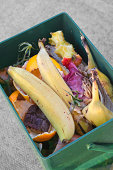Fruit and vegetable waste in a green plastic caddy ready for the compost heap.Kitchen waste from chopping board to compost bin; check out this Lightbox: