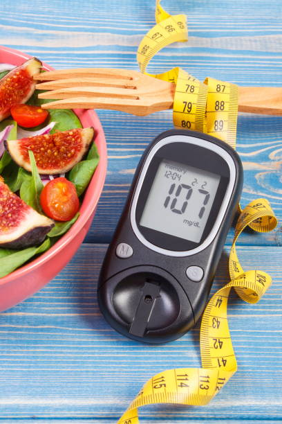 Fruit and vegetable salad and glucometer with result of sugar level, concept of diabetes, slimming and healthy nutrition stock photo