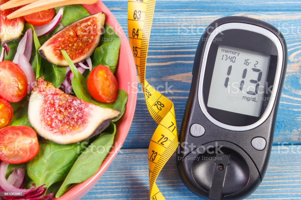 Fruit and vegetable salad and glucose meter with tape measure, concept of diabetes, slimming and healthy nutrition stock photo