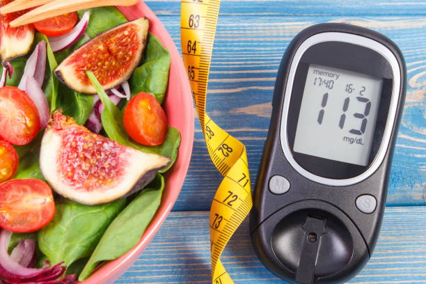 fruit and vegetable salad and glucose meter with tape measure, concept of diabetes, slimming and healthy nutrition - diabetic stock photos and pictures