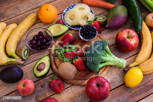 Fruits and vegetables assortment at wood table, shot from above