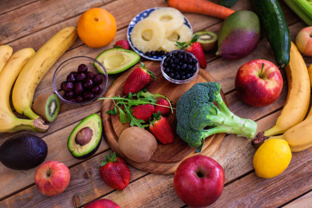 Fruit and veggies assortment at wood table, shot from above stock photo
